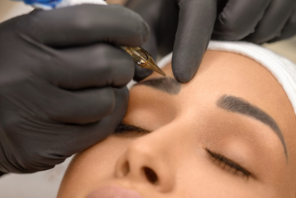 Beautiful young woman receiving microblading treatment on eyebrows