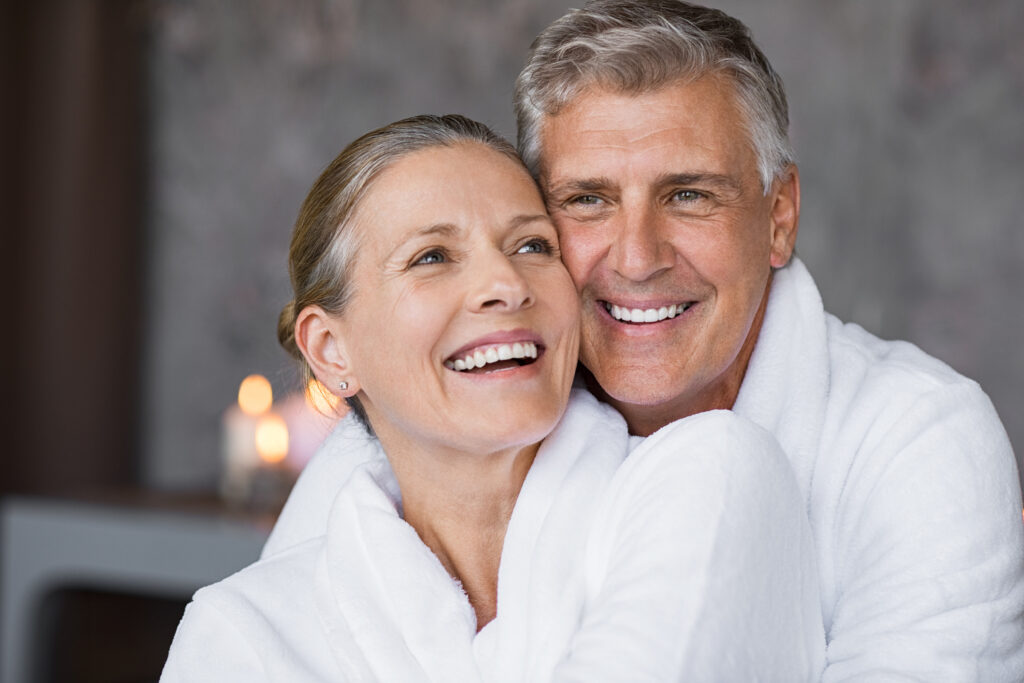 Smiling husband embracing cheerful wife from behind at medical spa for anti-aging treatments.